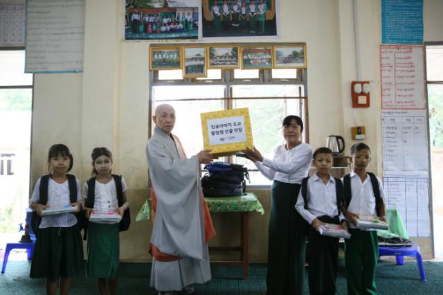 =5. 지구촌공생회 이사장 송월주 큰스님이 밍글라따지 초등학교 졸업생들을 위한 선물을 전달하고 있다..JPG